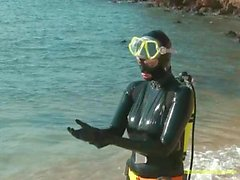 Dressing in black latex catsuit & diving gear then swimming at the beach
