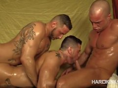 Three shining oiled bodies in the massage room
