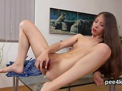 Ravishing girl is pissing and pleasing hairless snatch